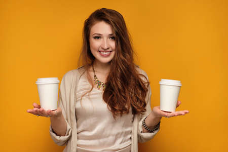 Red-haired girl stands on a yellow background smiling looking at the camera and holding two cups on the palms.