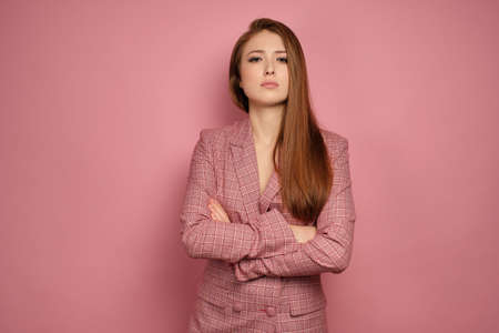 A redhead girl in a jacket stands on a pink background with arms crossed over chest and head haughtily looking at the camera.