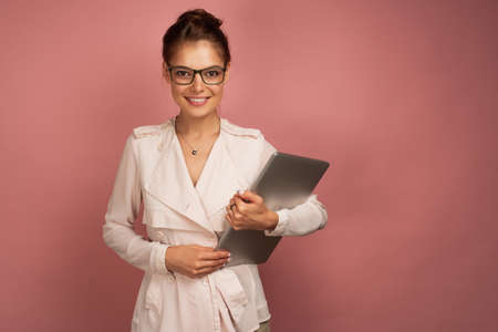 A girl in a light jacket and glasses openly smiling stands with a laptop on a pink background. Zdjęcie Seryjne