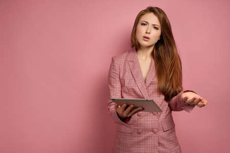 Red-haired girl in a business suit on a pink background and holding a laptop looking at the camera with displeasure. Фото со стока