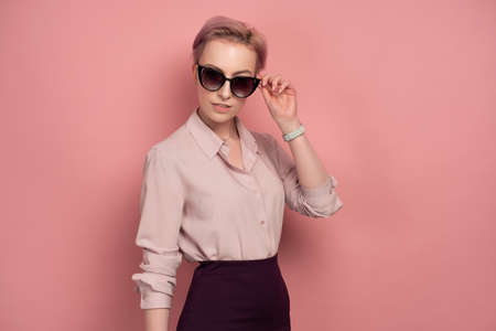 A girl with short pink hair in a blouse and skirt stands on a pink background, adjusting her sunglasses.
