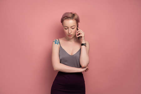 A girl with short pink hair and a tattoo in a gray top and speaks on the phone, looking down, standing on a pink background.