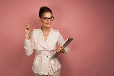 A girl in a light jacket and glasses stands on a pink background with a laptop and looks up at the camera with his index finger up 스톡 콘텐츠 - 129418328