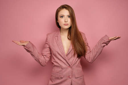 Redhead girl in a jacket stands on a pink background with arms outstretched to the sides and wide-open eyes looking at the camera Фото со стока