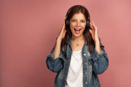 A girl in a jeans shirt stands on a pink background, clutching headphones and joyfully opening her mouth, looking at the camera. Фото со стока
