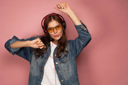 A dark-haired girl in jeans stands on a pink background with headphones, dancing, looking at the camera.