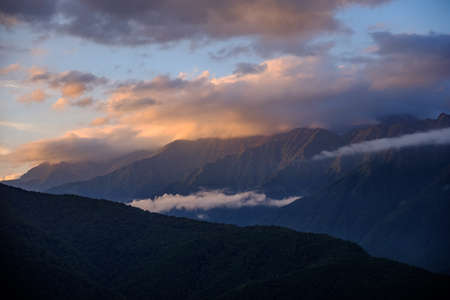 Mountain ranges in the clouds at sunset.