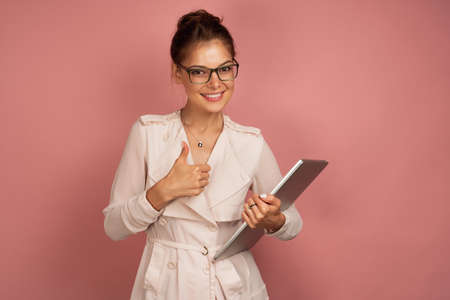 A girl in a light jacket and glasses openly smiling is standing with a laptop on a pink background, thumb up.