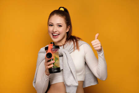 Red-haired girl in a short top is standing on a yellow background with a sports shaker and shows thumb up, laughing. Imagens