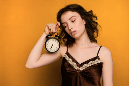 A curly dark-haired girl stands on a yellow background in a brown top and sleepily looks at the alarm clock in her hand. Standard-Bild