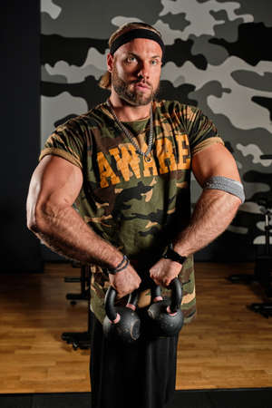 A muscular man in a sports shirt with a military print stands with kettlebells in his hands in the gym Imagens