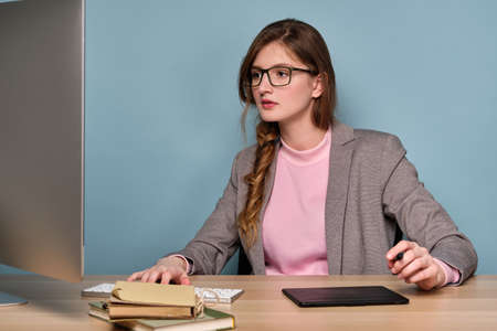 A girl in a pink sweater, a gray jacket and glasses sits at a table, carefully looks at the monitor.