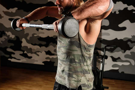 Muscular man raises the barbell to the chest, large frame
