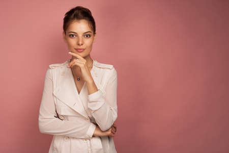A dark-haired girl in a light jacket stands thoughtfully on a pink background and looks at the camera.