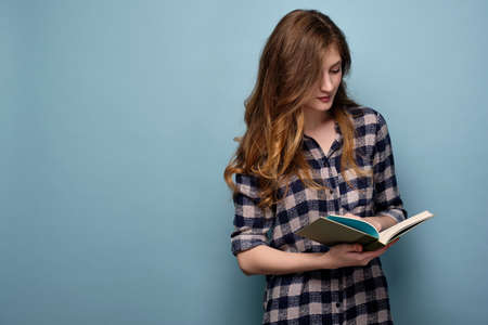 A young girl in a plaid shirt stands on a blue background and looks down in a book with his head bowed.