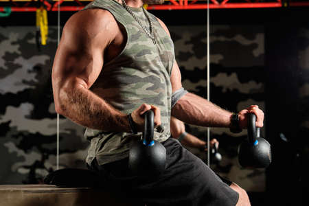 Close-up shot of male inflated torso and muscular arms with kettlebells in the gym Imagens
