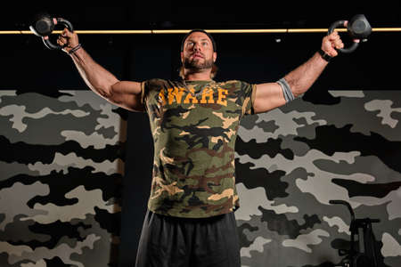 A muscular man in a sports T-shirt stands against a wall with a military print, spreading a palm with kettlebells to the side