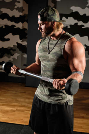 Muscular man in a T-shirt and a baseball cap holds the barbell in bent arms, vertical frame