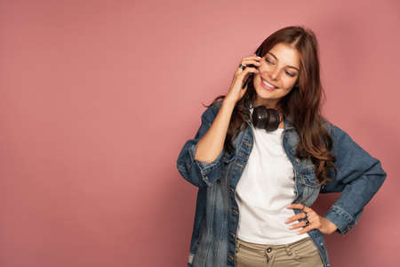 A girl in jeans stands on a pink background with headphones on her neck and speaks on the phone with a smile looking down