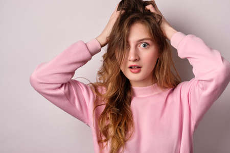 A blonde girl in a pink sweatshirt stands on a white background and looks in horror at the frame ruffling her hair
