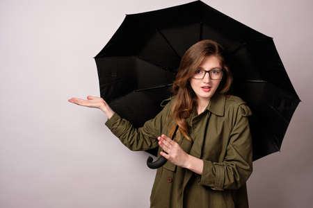 A blonde girl with glasses and a raincoat is standing with a black umbrella and is pointing with surprise with her hand to the side