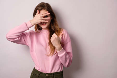 A blonde girl in a pink sweatshirt and looks through her fingers smiling at the frame and showing her fingers to the side Stock Photo