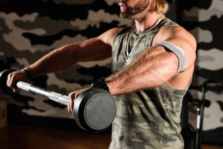 Close-up shot of a barbell in male hands during a workout