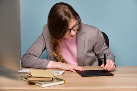 A girl in a pink sweater, gray jacket and glasses sits at a table, bowing her head, draws on an electronic tablet. Stock Photo