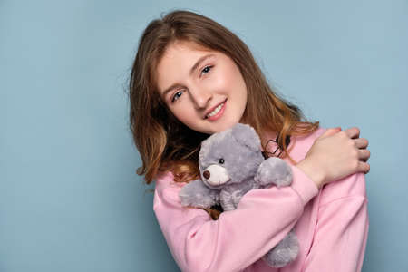 A girl in a pink sweater stands ona blue background and smiling, presses a bear toy to her. Stock Photo