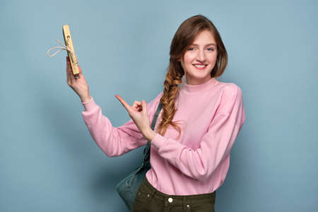 A girl in a pink sweater with a backpack stands on a blue background and holds a book in her hand and points a finger at it.