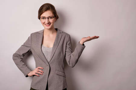 Blonde girl in glasses and a gray jacket with stands on a white background, points with the palm to the side and smiles Stock Photo
