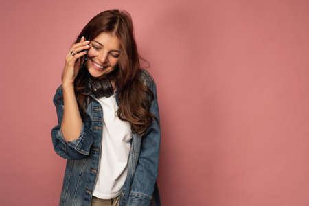 A beautiful girl in a denim with headphones on her neck speaks on the phone shyly laughing.