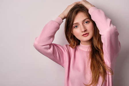 A blonde girl in a pink sweatshirt stands on a white background and looks into the frame with her hands on her head