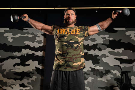 A muscular man in a sports T-shirt with a military print is standing holding his weights in apart hands Imagens