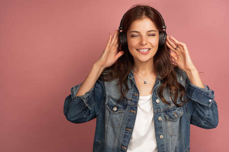 A dark-haired girl in a jeans stands on a pink background in the headphones, smiling broadly and closing her eyes, biting her lip.