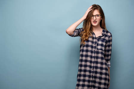 A young girl in a plaid dress and glasses stands on a blue background and looks in camera in surprise with his mouth open.