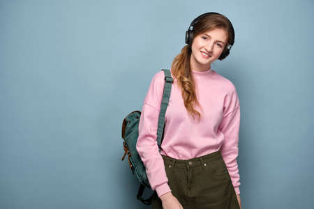 A young girl in a pink sweater and headphones with a backpack stands on a blue background and smiles at the camera.