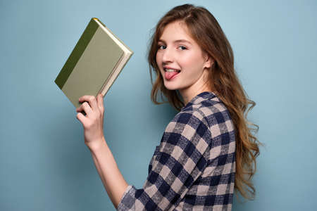 A girl in a plaid dress stands on a blue background looking at the camera and sticking out her tongue, holding a book in her hand. Stock Photo