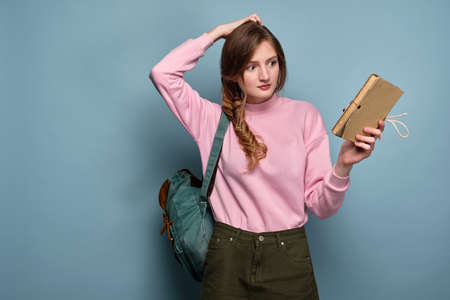A girl in a pink sweater with a backpack stands on a blue background and holds a book, looking puzzled at her, scratching her head