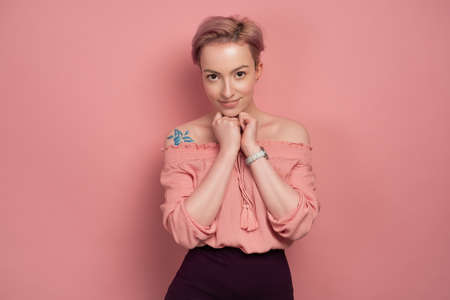 A girl with short pink hair stands on a pink background, smiling cute, looking at the camera, clutching her hands to her chest. Stock Photo