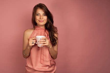 A brunette stands on a pink background in a dress holding a mug in her hands and is smiling pretty at the camera.