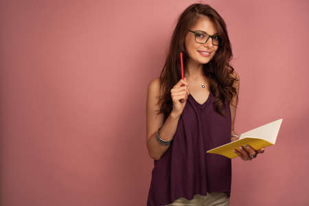 A dark-haired girl in a purple top and glasses stands on a pink background with a notebook and pencil, looks at the camera.