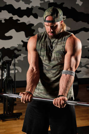 Muscular man in a military t-shirt with a print and a baseball cap holds the barbell in his hands, his head down Imagens