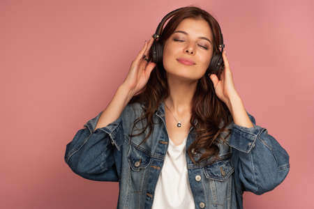 A charming girl in a jeans stands on a pink background with pleasure watching music with her eyes closed. Stock Photo