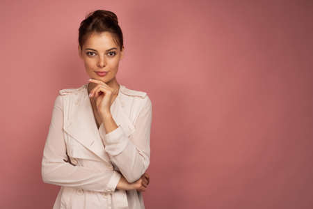 Brunette girl in a light jacket with gathered hair stands on a pink background and looks at the camera, propping chin with hand Stock Photo