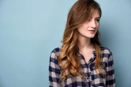 A young girl in a plaid shirt stands on a blue background and looks to the side.