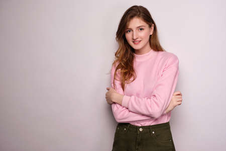 A girl in a pink sweater stands on a white background, looks at the camera, cross her arms over her chest.