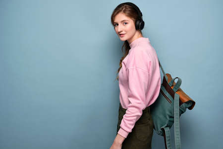 A young girl in a pink sweater with a backpack and headphones stands in profile on a blue background.