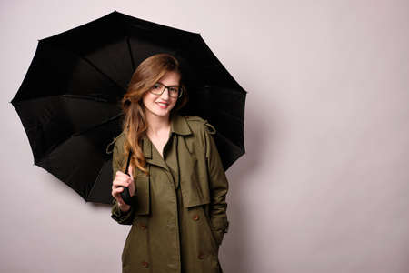 A blonde girl in glasses and a raincoat is standing with a black umbrella and smiling at the camera with her hand in her pocket
