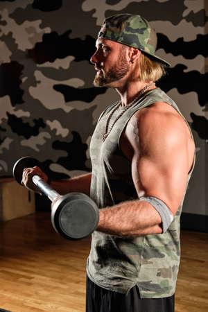 Muscular man in a T-shirt and a baseball cap raises the bar, vertical frame
